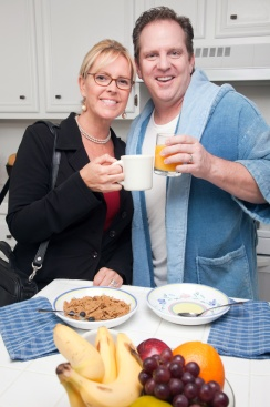 Businesswoman Ready for Work with Husband In Kitchen.